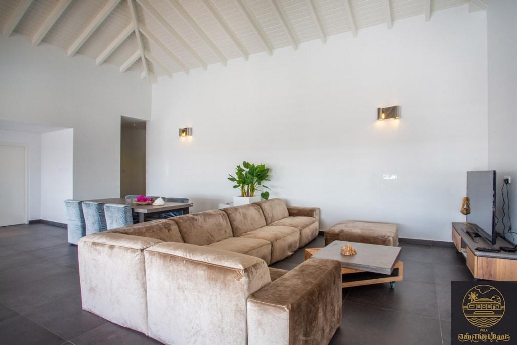 Vakantievilla Curacao huren? De modern ingericht woonkamer van de villa - Grote bank waarop meerdere mensen lekker kunnen chillen